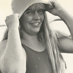 Faded photo of Lynne Cox, smiling, wearing a swimsuit, and pulling a swim cap over her head.