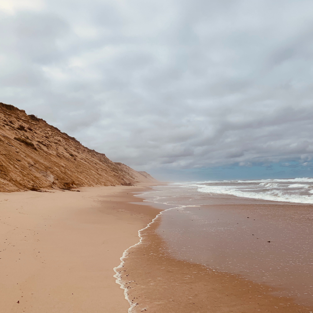 An empty beach with steep reddish-brown dunes on the left and the ocean to the right, with a slightly overcast sky