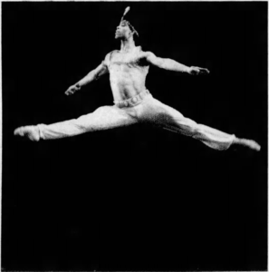 Carlos Acosta as a young man, performing in a ballet, mid-leap.