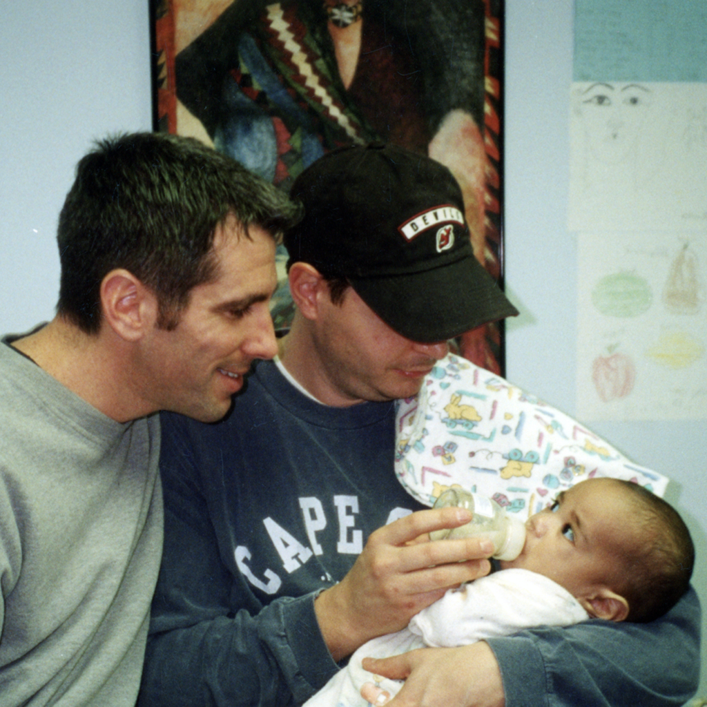 Two men holding a baby, gazing down at him and feeding him a bottle.