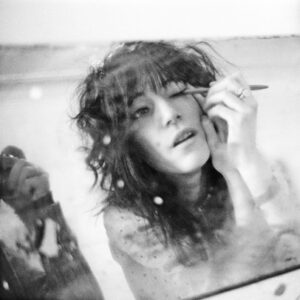 A black and white photograph of Patti Smith applying eye makeup with a pencil, all reflected in a mirror. In the corner of the photograph you can see a reflection of the photographer's arm holding the camera.