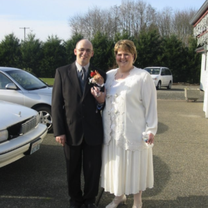 Jeff Ingram and Penny Hansen on their wedding day, standing together in a parking lot and smiling. Jeff is wearing a suit and holding a small dog, and Penny is wearing a white dress and cardigan.