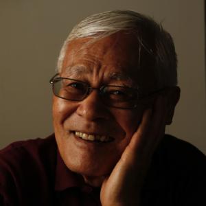 Close-up portrait of Shigeru Yabu, smiling, resting his cheek in his hand.