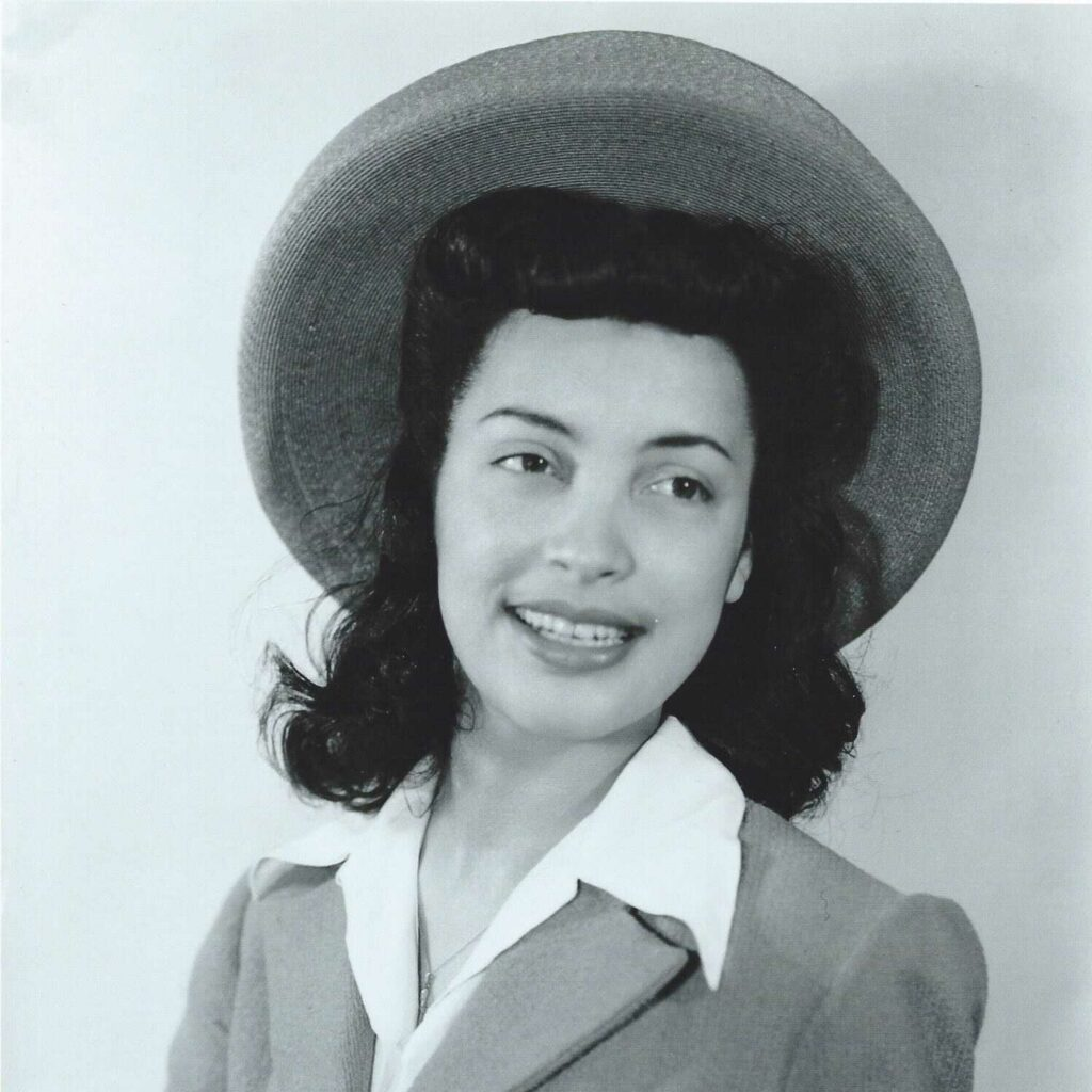 Black and White portrait photo of a young Betty Reid Soskin smiling, and wearing a hat and a suit. with